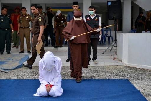 This file photo taken on Dec. 10, 2019 shows the first female flogger preparing to whip a woman in public, in Banda Aceh, after she was caught in close proximity with a man who is not her husband in a hotel. With more women being charged for morality crimes in recent years, Aceh says it's trying to follow Islamic law that calls for women to whip female perpetrators -- which is the case in neighbouring Malaysia.