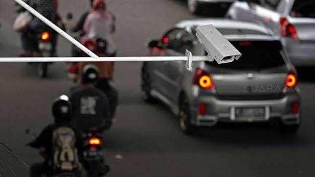 Pengendara melintas di bawah alat Automatic Number Plate Recognition (ANPR) perempatan lampu merah Kuningan-Mampang Jakarta, Sabtu (22/11).