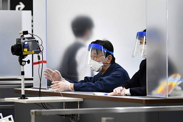 Officers wearing face masks and shields, amid concerns about the spread of the COVID-19 novel coronavirus, monitor passengers arriving at Narita airport, Chiba prefecture on March 9, 2020.