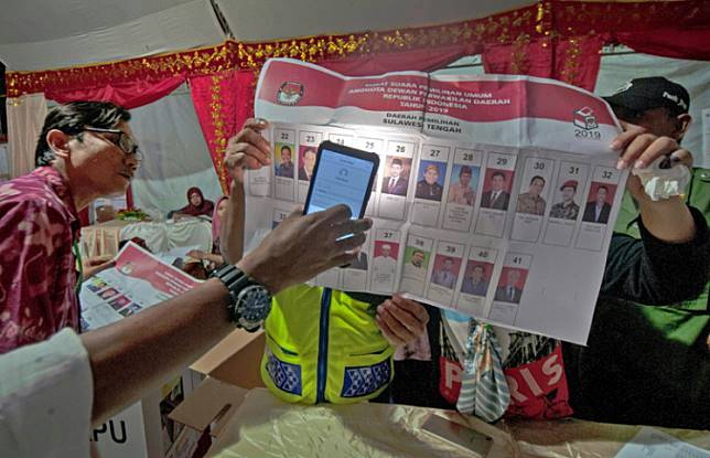 Night reader: A local poll administrator (KPPS) uses a smartphone to check ballots during the vote count on Wednesday in Lolu Utara, Palu, Central Sulawesi. The vote count ended after midnight.