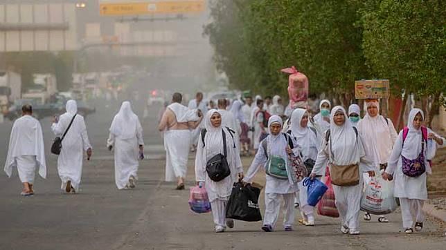 Sejumlah muslim membawa barang bawaannya saat berjalan menuju Masjid Namirah di Gunung Arafat, selama melaksanakan ibadah haji, di luar Kota Suci Mekah, Arab Saudi, 19 Agustus 2018. Pemberangkatan jemaah haji akan dilakukan secara bergelombang untuk menghindari penumpukan jemaah. AP
