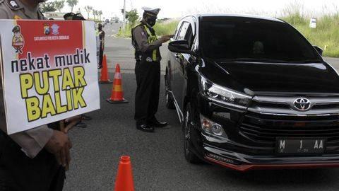Petugas memeriksa kelengkapan surat dan KTP saat hari pertama penyekatan larangan mudik di Perbatasan Surabaya-Sidoarjo di Tambak Sumur, Sidoarjo, Jawa Timur, Kamis (6/5/2021). (ANTARA FOTO/Umarul Faruq)