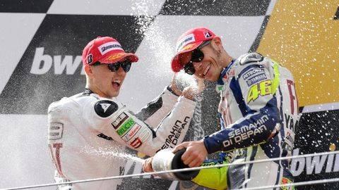 Jorge Lorenzo dan Valentino Rossi saat selebrasi bersama di atas podium. (Foto: FRANCISCO LEONG / AFP)