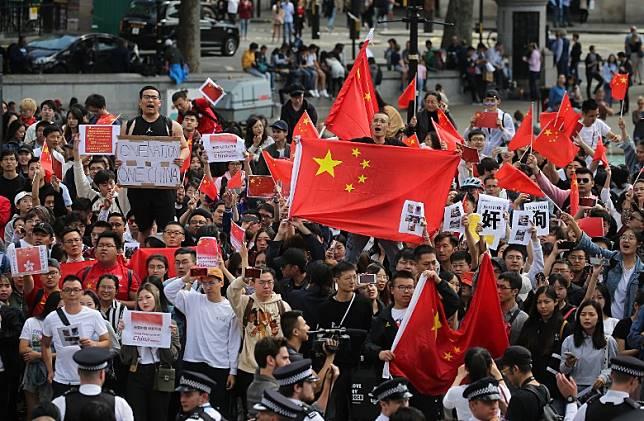 與偷敦遊行人士打對台的親中華人舉起五星紅旗。(法新社圖片)