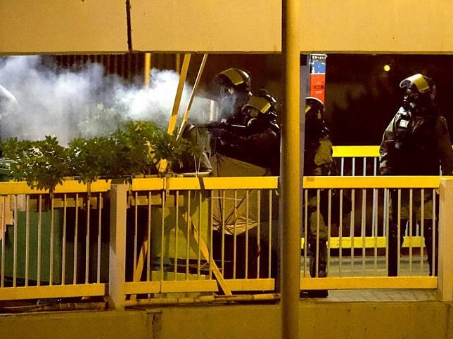防暴警察在天橋向示威者發射催淚彈。(美聯社)