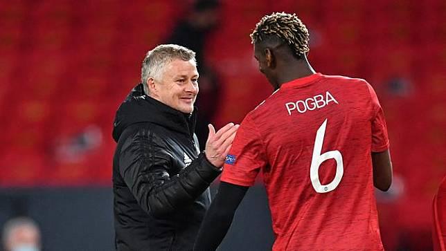 Manajer Manchester United, Ole Gunnar Solskjaer, bersama Paul Pogba, setelah kemenangan telak 6-2 atas AS Roma di leg pertama semifinal Liga Europa, Jumat (30/4/2021) dini hari WIB. (Paul ELLIS / AFP)