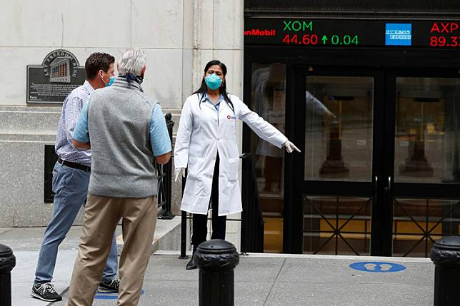 Medical personnel speak to men as they arrive outside the New York Stock Exchange as the building opens for the first time since March on May 26. Reuters' analysis of public data found around 110 publicly traded companies have each received $4 million or more in emergency aid from the $660 billion Paycheck Protection Program (PPP) — an economic rescue package, meant to save small firms convulsed by the pandemic and help them to keep workers on the payroll.