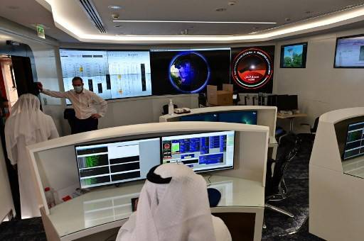 In this file photo taken on July 05, 2020 employees work at the control room of the Mars Mission at the Mohammed Bin Rashid Space Centre (MBRSC), in the Gulf emirate of Dubai. - The oil-rich United Arab Emirates has built a nuclear power programme and sent a man to space, and now plans to join another elite club by sending a probe to Mars. Only the United States, India, the former Soviet Union, and the European Space Agency have successfully sent missions to orbit the Red Planet, while China is preparing to launch its first Mars rover later this month. The UAE, a collection of sheikhdoms better known for its skyscrapers, palm-shaped islands and mega attractions, is now pushing to join their ranks in what will be a first for the Arab world.