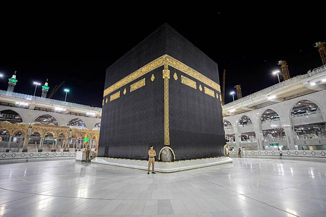 Saudi security officers stand in front of the Kaaba at empty Grand mosque, as a preventive measure against the COVID-19, during the holy month of Ramadan, in the holy city of Mecca, Saudi Arabia May 5, 2020. Saudi Arabia announced health protocols to prevent the spread of the new coronavirus in the 2020 haj season, banning gatherings and meetings between pilgrims, the state news agency said on Monday.