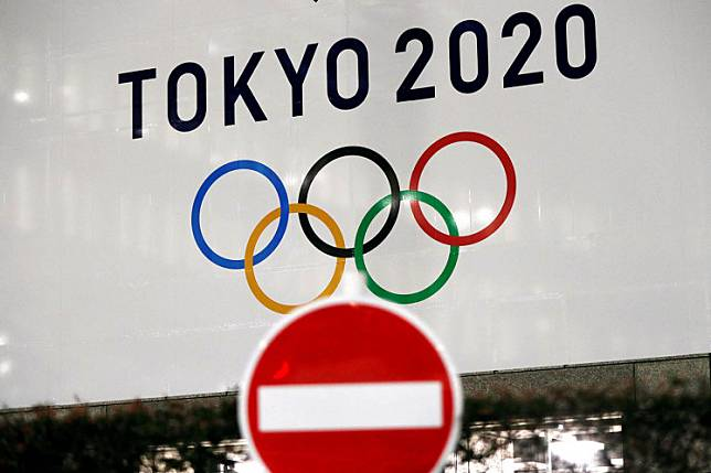 A banner for the upcoming Tokyo 2020 Olympics is seen behind a traffic sign, following an outbreak of the COVID-19, in Tokyo, Japan, March 23, 2020.The rearranged Tokyo Olympics are likely to be a pared-down version of recent editions of the four-yearly Games, Japanese Olympic Committee chairman Yasuhiro Yamashita said on Tuesday.