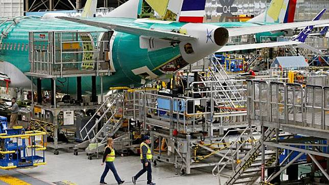 Employees walk by the end of a 737 Max aircraft at the Boeing factory in Renton, Washington, U.S., March 27, 2019.