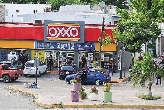Sejumlah pria bersenjata kartel narkoba berdiri di luar sebuah toko selama baku tembak dengan pasukan federal menyusul penahanan Ovidio Guzman, putra gembong narkoba Joaquin