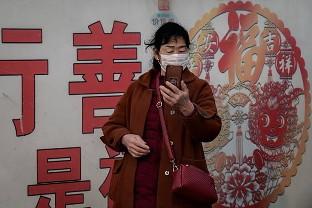 A woman wearing a protective mask to help stop the spread of a deadly virus which began in Wuhan, looks at her smartphone at the Beijing railway station in Beijing on January 27, 2020. - China on January 27 extended its biggest national holiday to buy time in the fight against a viral epidemic and neighbouring Mongolia closed its border, after the death toll spiked to 81 despite unprecedented quarantine measures.