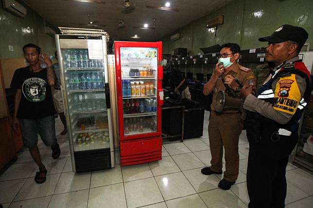 Officials from the Surabaya Police and city administration disperse visitors at an internet cafe in Surabaya, East Java on March 23. Law enforcement and regional officials have advised residents hanging out across the city to go home  to curb COVID-19 transmission in the city.