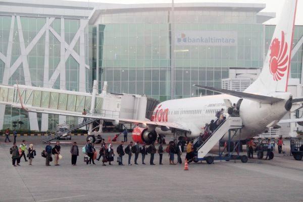 Sejumlah calon penumpang antre naik ke pesawat maskapai Lion Air di Bandara Internasional Sultan Aji Muhammad Sulaiman Sepinggan