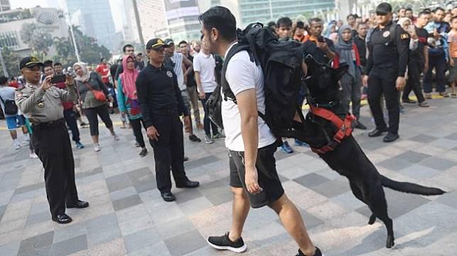 Anjing pelacak dari Unit K-9 Polri mengendus adanya bom yang dibawa oleh seseorang di dalam tasnya saat simulasi di kawasan hari bebas kendaraan bermotor atau car free day (CFD) di Jalan MH Thamrin, Jakarta, Minggu (19/1).  [ANTARA FOTO/Akbar Nugroho Gumay]