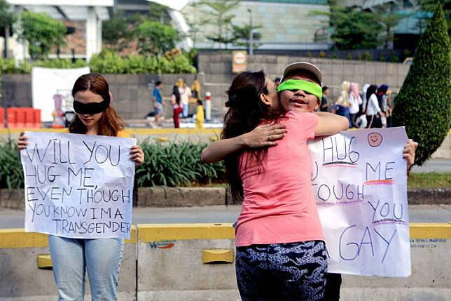 A passerby hugs an activist campaigning for the rights of the lesbian, gay, bisexual and transgender (LGBT) community during Car Free Day in Jakarta.