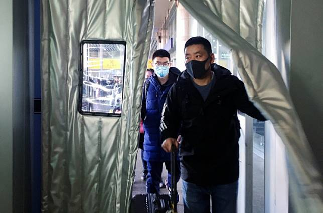 Near, far, wherever you are: Passengers wearing masks enter the Beijing West Railway Station in Beijing on Monday. Chinese authorities said the number of patients of an outbreak of a new coronavirus in the country had tripled and a third person had died.