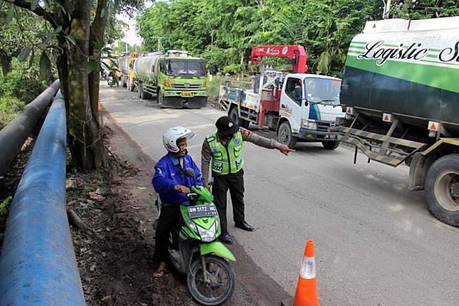 Petugas memberhentikan kendaraan di pos penyekatan (ilustrasi).
