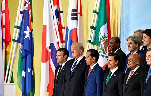 (Left to right) French President Emmanuel Macron, US President Donald Trump, President Joko Widodo, Mexico's President Enrique Pena Nieto, German Chancellor Angela Merkel, China's President Xi Jinping, Russia's President Vladimir Putin, Britain's Prime Minister Theresa May, and Turkey's President Recep Tayyip Erdogan line up for a family photo of the participants of the G20 summit in Hamburg, northern Germany.