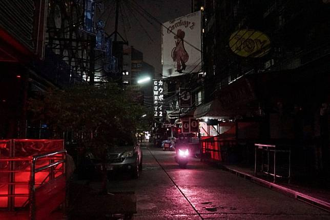 This photo taken on April 4, 2020 shows a motorbike passing through the closed down Soi Cowboy street in Bangkok, a road usually busy with sex workers and customers but now closed for business as authorities seek to halt the spread of the COVID-19 coronavirus. A shutdown to contain the coronavirus has killed Thailand's party scene and forced sex workers out of bars and onto desolate streets.