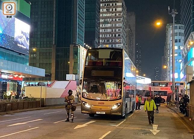 巴士死火停在路中,警員持槍戒備。(何青霞攝)