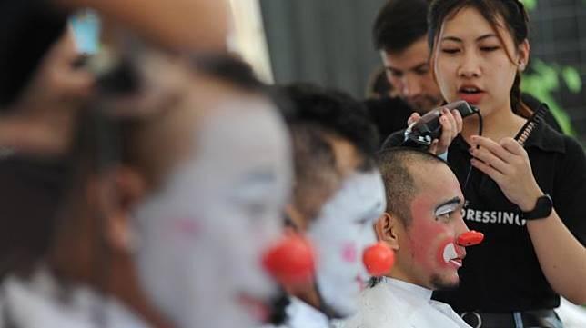 Anggota komunitas Aku Badut Indonesia menggunduli rambutnya untuk berdonasi bagi anak-anak penderita kanker di Gandaria City Mall, Jakarta, Minggu (16/2).  [ANTARA FOTO/Indrianto Eko Suwarso]