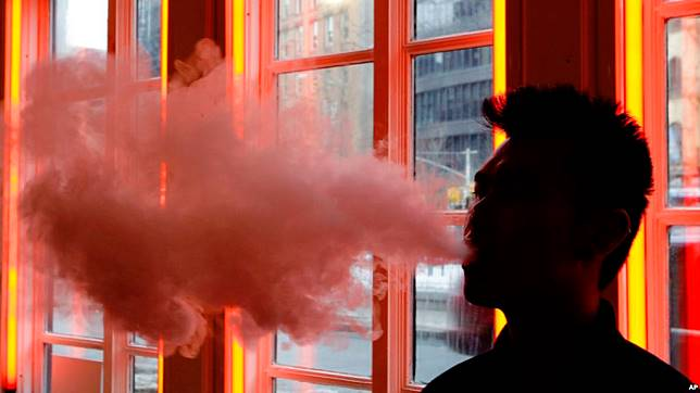 FILE - A customer exhales vapor from an e-cigarette at a store in New York, Feb. 20, 2014.