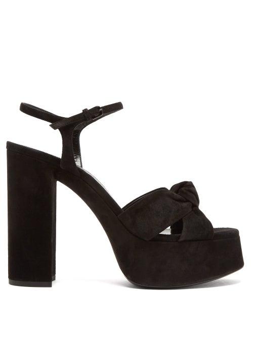 Saint Laurent - The towering silhouette of Saint Laurent's black Bianca sandals taps the enduring 19