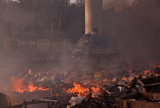 A police vehicle moves past burning debris that was set on fire by demonstrators in a riot affected area after fresh clashes erupted between people demonstrating for and against a new citizenship law in New Delhi, India, Feb. 25, 2020.