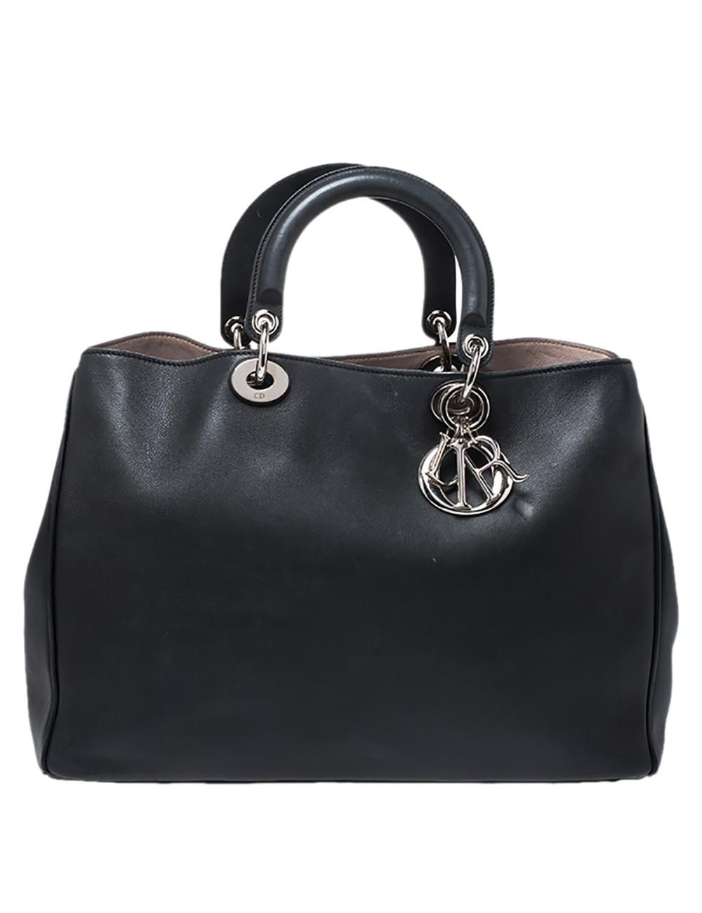 Dior Diorissimo購物手提袋是一件永不過時的作品。皮革包採用令人愉悅的黑色調,配以銀色金屬配件和Dior字母飾物。它具有雙頂提手,一個小袋和底部的保護腳。按扣開合打開,露出帶有皮革襯裡的內