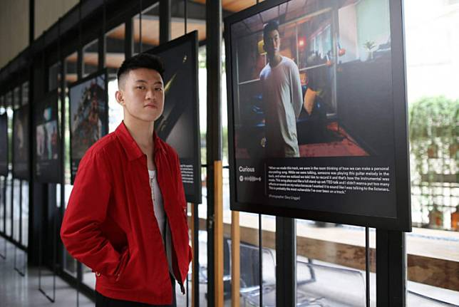 Brian 'Rich Brian' Immanuel poses beside one of the photos displayed at The Sailor Exhibition in August 2019 in Jakarta.