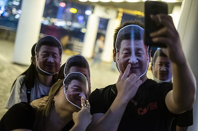 Demonstrators wearing face masks featuring Chinese President Xi Jinping pose for a selfie photograph during an event in the Tsim Sha Tsui district of Hong Kong. Photographer: Justin Chin/Bloomberg