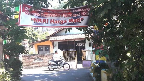 "A motorist passes by a banner which says ""Residents of Candi district in Semarang refuse Papua's separation from Indonesia. NKRI [the Unitary State of the Republic of Indonesia] is undisputed"" in front of a dormitory for Papuan students in Semarang, Central Java."