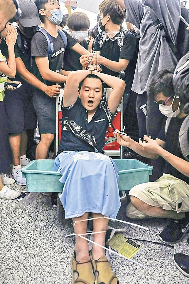 一名男子被示威者用索帶綁起毆打,事後證實是內地《環球時報》記者付國豪。