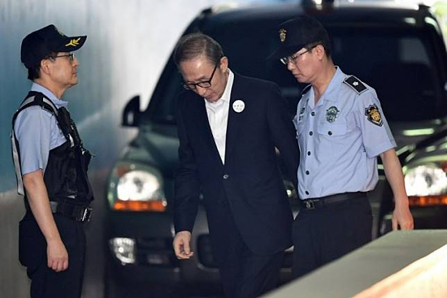 Former South Korean president Lee Myung-bak (center) arrives at a court to attend his trial in Seoul in this Sept. 6, 2018 file photo. He was taken to prison Wednesday to begin a 17-year term for bribery and embezzlement after losing an appeal against a lighter sentence.