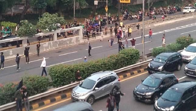 Massa aksi demonstrasi menolak Rancangan Undang-undang (RUU) Omnibus Law Cipta Kerja di depan Gedung DPR, Jakarta memanas, Kamis (16/7/2020) petang. (Foto: Rico Afrido/ Sindo Media).