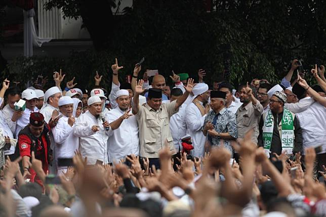 Prabowo (center, in black cap and beige top) addresses hundreds of supporters during a mass prayer held on April 19, just two days after the election, at his residence in South Jakarta.