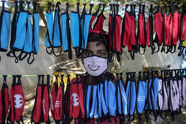 A street vendor poses as he arranges facemasks to sell on the roadside as a preventive measure against the spread of the COVID-19 coronavirus on the outskirts of Hyderabad on June 5, 2020.
