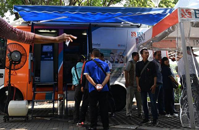 Customers queue to exchange their banknotes at a Bank Indonesia mobile service outlet at the National Monument (Monas) park in Central Jakarta on May 13.
