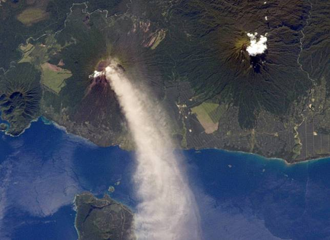 """This NASA Observatory International Space Station astronaut photograph obtained December 11, 2012, was taken during the most recent phase of volcanic activity at Ulawun acquired on November 30, 2012. A plume of white steam and ash extends from the summit crater of the stratovolcano towards the northwest. The plume begins to broaden as it passes the southwestern coast of Lolobau Island, approximately 23 kilometers downwind. Note that the image is oriented such that north is towards the lower left. Ulawun is also known as """"the Father,"""" with the Bamus volcano to the southwest also known as """"the South Son."""" The summit of Bamus is obscured by white cumulus clouds (not of volcanic origin) in this image. While Ulawun has been active since at least 1700, the most recent activity at Bamus occurred in the late 19th century. A large region of ocean surface highlighted by sunglint—sunlight reflecting off the water surface—is visible to the north-northeast of Ulawun. Numerous volcanoes contribute to the landmass of the island of New Britain, the largest in the Bismarck Archipelago of Papua New Guinea. One of the most active of these volcanoes—Ulawun—is also the tallest, with a summit elevation of 2,334 meters (7,657 feet)."""