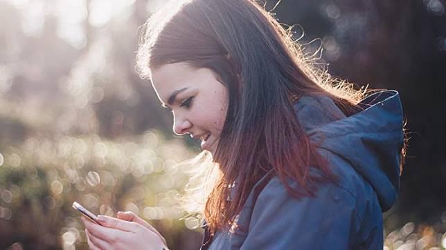 Ilustrasi remaja perempuan sedang melihat gawai. (Unsplash/Luke Porter)