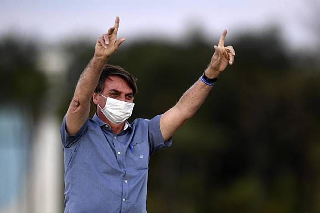 Brazilian President Jair Bolsonaro gestures while attending the flag unveiling ceremony at the Alvorada Palace in Brasilia, on July 17, 2020, amid the new coronavirus pandemic.
