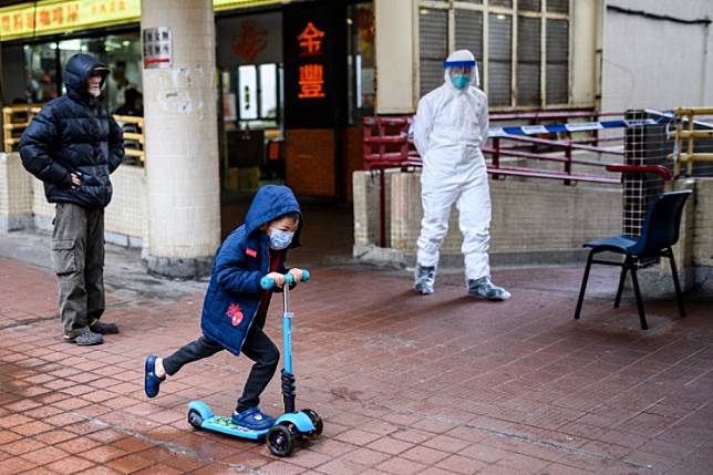 A child wearing a face mask rides his scooter past a police officer wearing protective gear outside Hong Mei House at Cheung Hong Estate in Hong Kong on Feb. 11, 2020. With schools closed, some expat families decide it's now time to leave town.