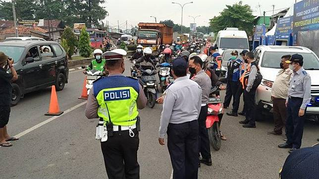 Penyekatan jalur mudik yang dilakukan pihak keamanan untuk pengendara sepeda motor di ruas jalan simpang Tanjung Pura, Karawang, Jawa Barat, Kamis (6/5/2021).