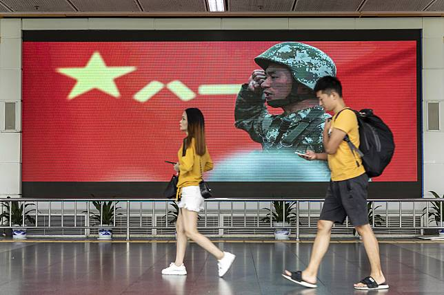Pedestrians walk past an advertisement for the PLA on a screen near the Luohu border crossing in Shenzhen. Photographer: Qilai Shen/Bloomberg
