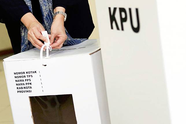 Boxed up: A KPU commissioner holds up a cardboard ballot box at the KPU headquarters in Jakarta on Dec. 14, 2018.