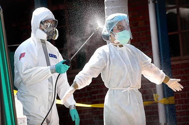 新冠肺炎本土疫情持續蔓延,許多民眾21日前往設在萬華青草廣場的篩檢站採檢,站內陸軍化學兵正在為護理人員進行全身消毒。(圖/范揚光攝)