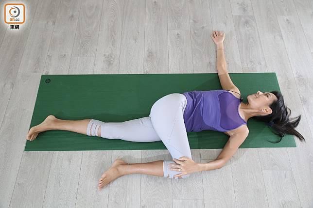 如覺得可再增加難度,可將右膝攬實到右邊膊頭方向,右邊腳可放鬆,但下邊左腳嘗試勾起腳趾去活動左邊大腿。吸氣,呼氣時慢慢將右膝放向左邊,令到臀部好像已離開地下。將頭擰向相反方向,望向右邊,背部即時有伸展感覺,並可伸展臀部肌肉。(張錦昌攝)