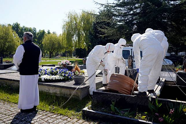 Father Marcos Rad officiates the funeral as municipal workers wearing protective gear lower the coffin of a victim of coronavirus disease (COVID-19) at El Salvador cemetery in Vitoria, Spain, on Friday.